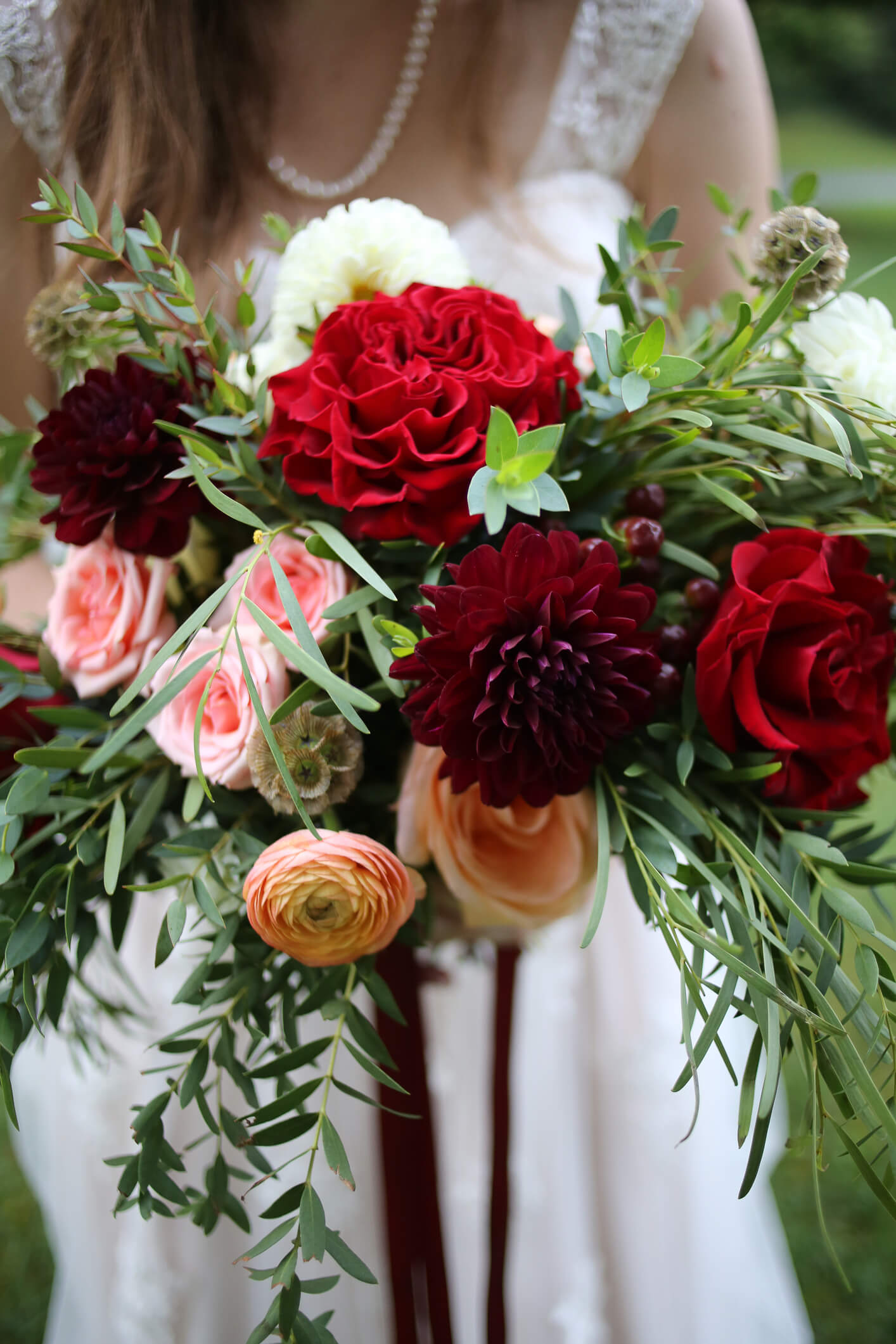 Bride Holding a Bouquet of Red, Maroon, Pink, Peach, and Yellow Flowers - Ranunculus, Roses, Dahlias