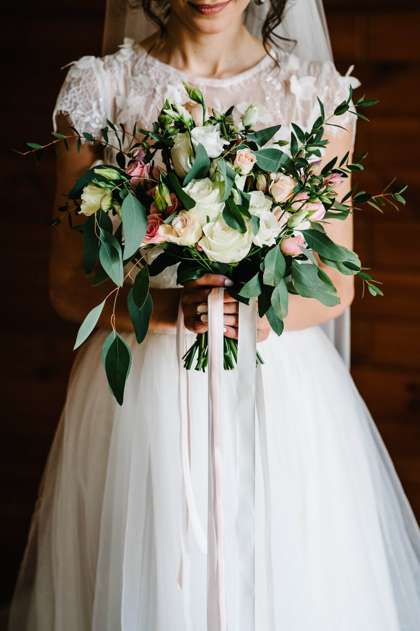 Bridal bouquet. Wedding. The girl in a white dress standing on a brown background and holds a beautiful bouquet of white, yellow, pink flowers and greenery, decorated with long silk ribbon.