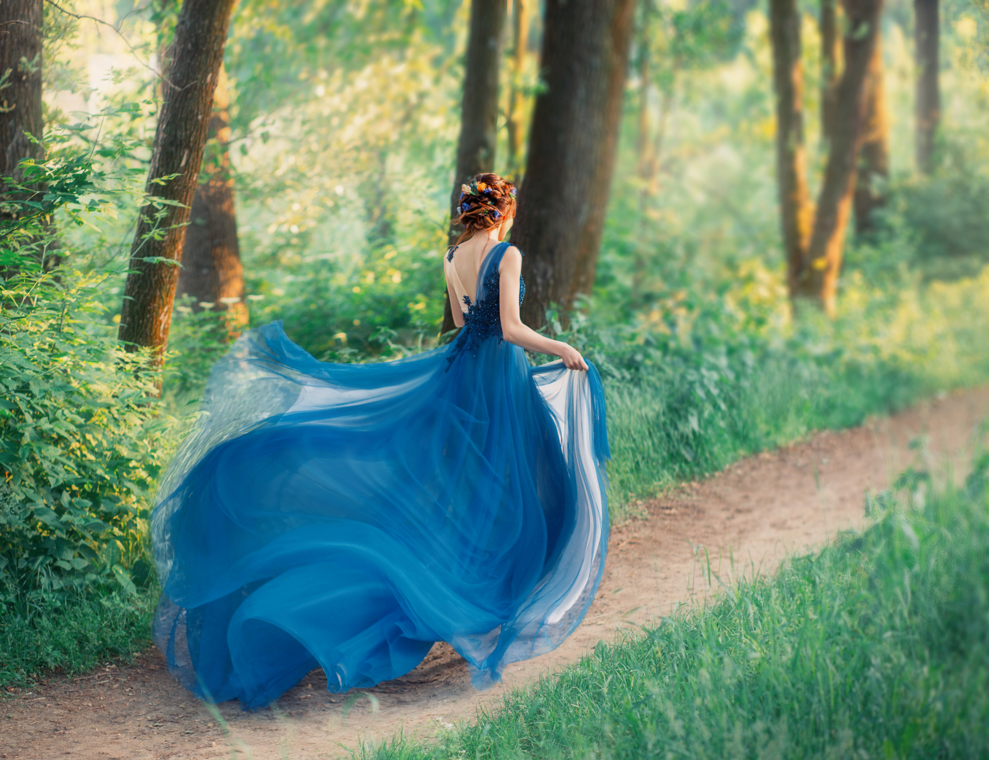 Lady in long elegant blue dress with flying light train