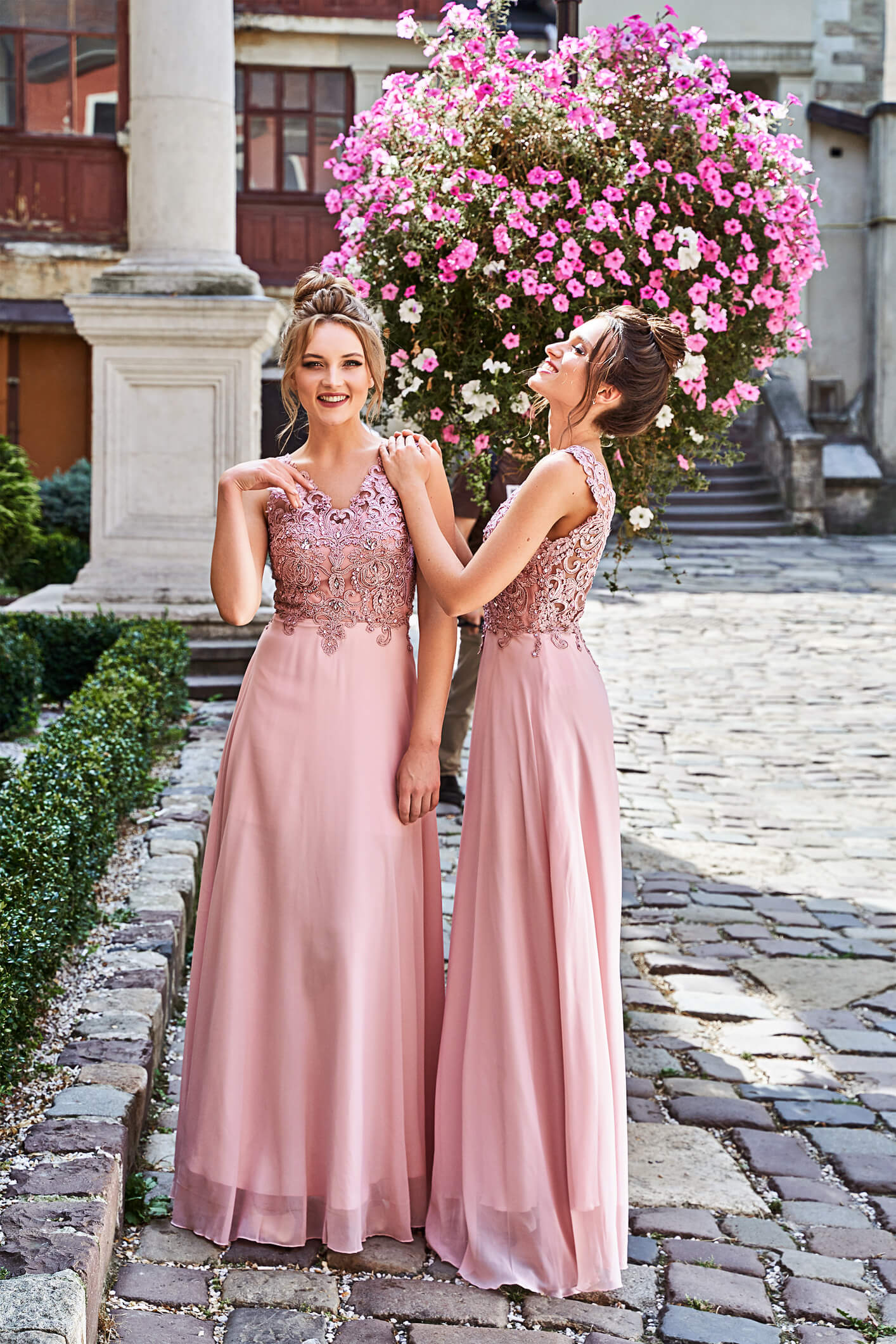 Beautiful blonde and brunette bridesmaids with luxury hairdo in gorgeous elegant stylish pale pink floor length v neck chiffon gown dress decorated with sequins sparkles and rhinestones on flowers background. Wedding day in old beautiful European city.