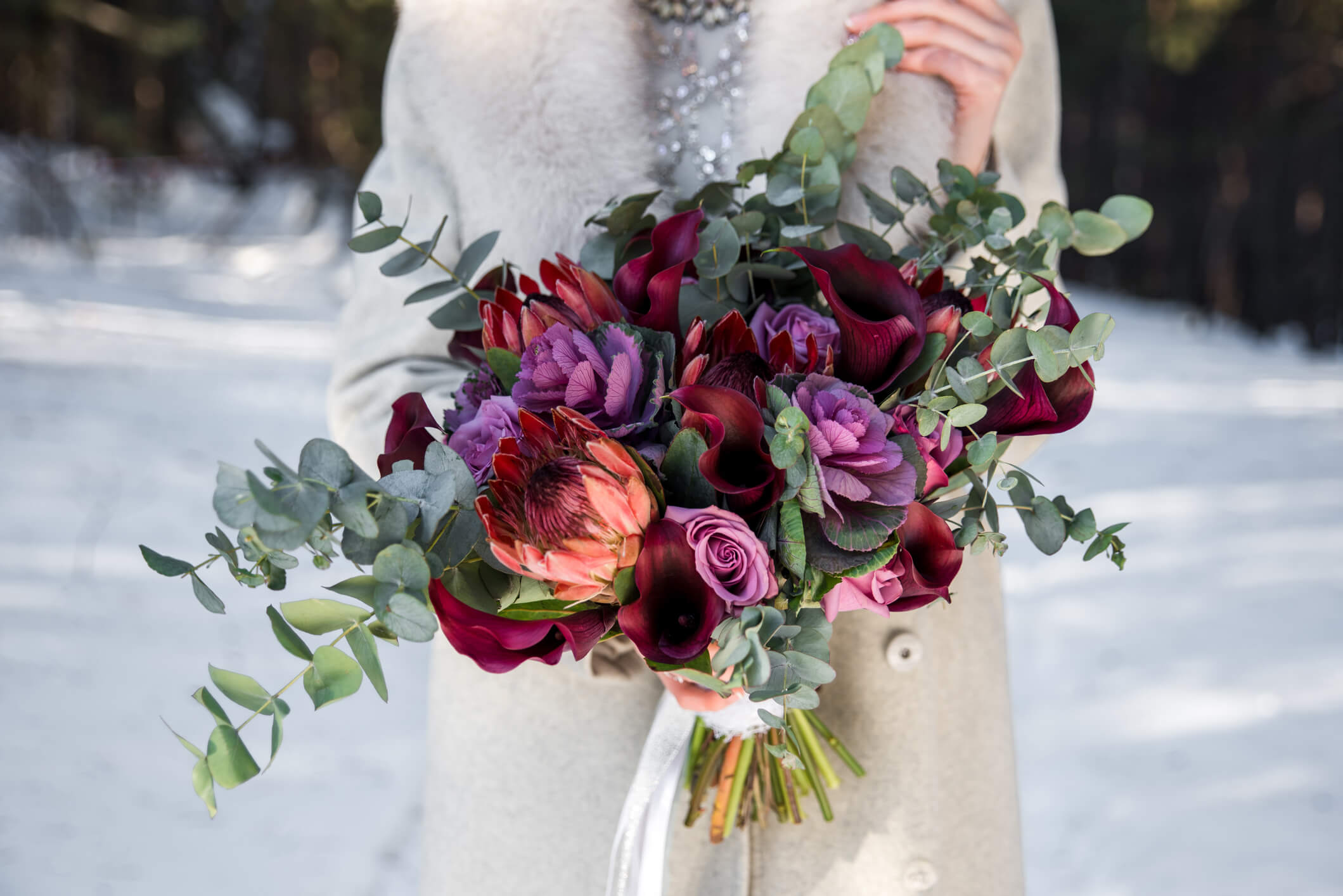 Lavender and dark red Wedding bouquet in hands of the bride
