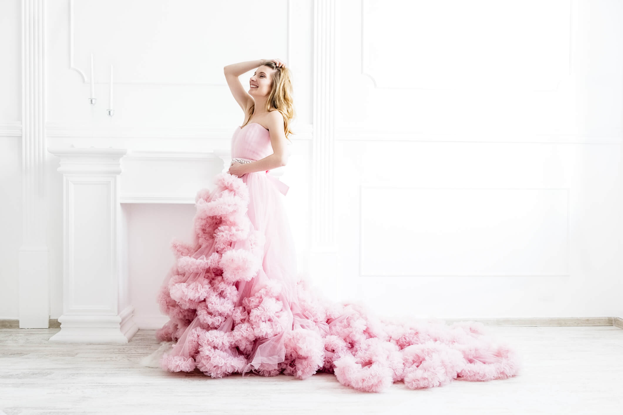 Dreamy woman portrait in a long pale pink ruffled gown in a white room.