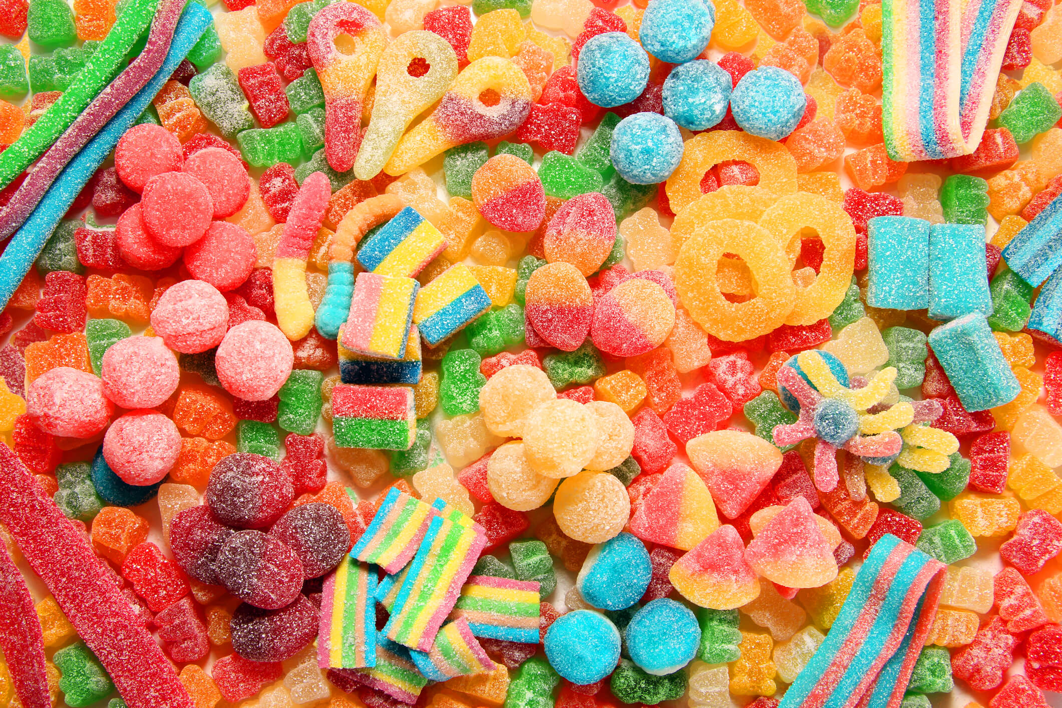 Assorted variety of sour candies includes extreme sour soft fruit chews, keys, tart candy belts and straws