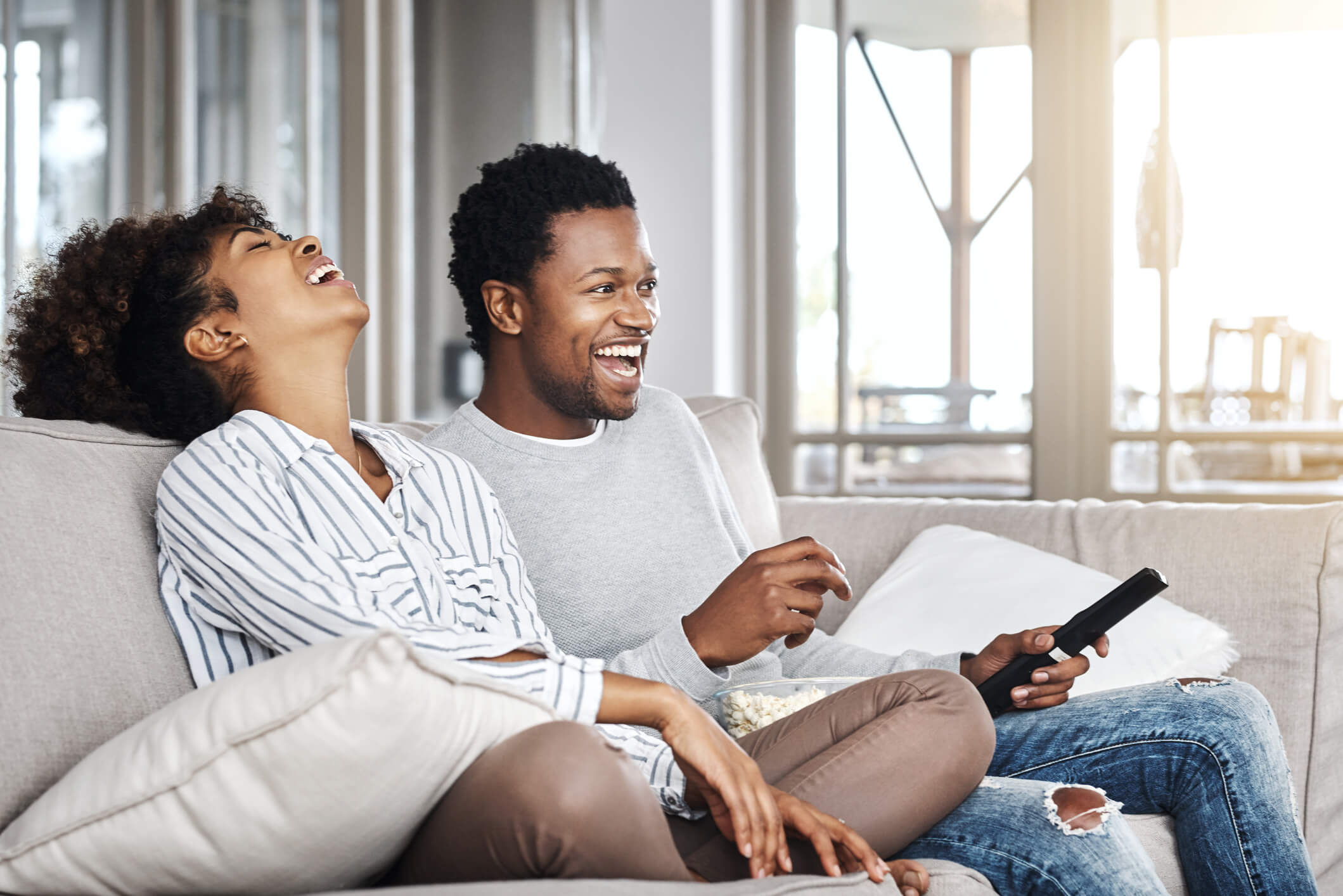 Shot of a happy young couple watching tv together at home